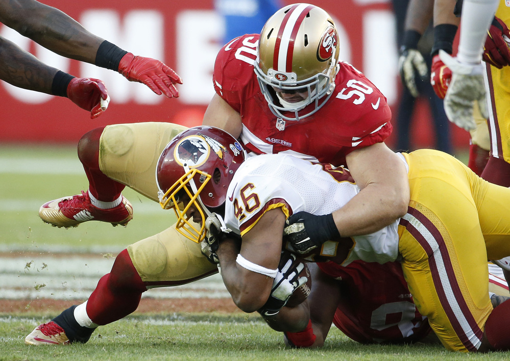 49er Chris Borland (50) tackles Washington Redskins running back Alfred Morris (46) in a game last fall.