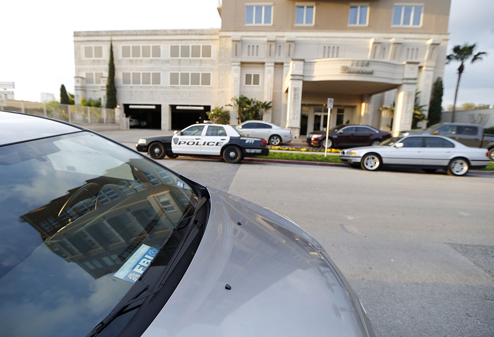 Police cars and a vehicle with a Federal Bureau of Investigation placard sit outside the building where Robert Durst owns some condominiums Tuesday in Houston.
