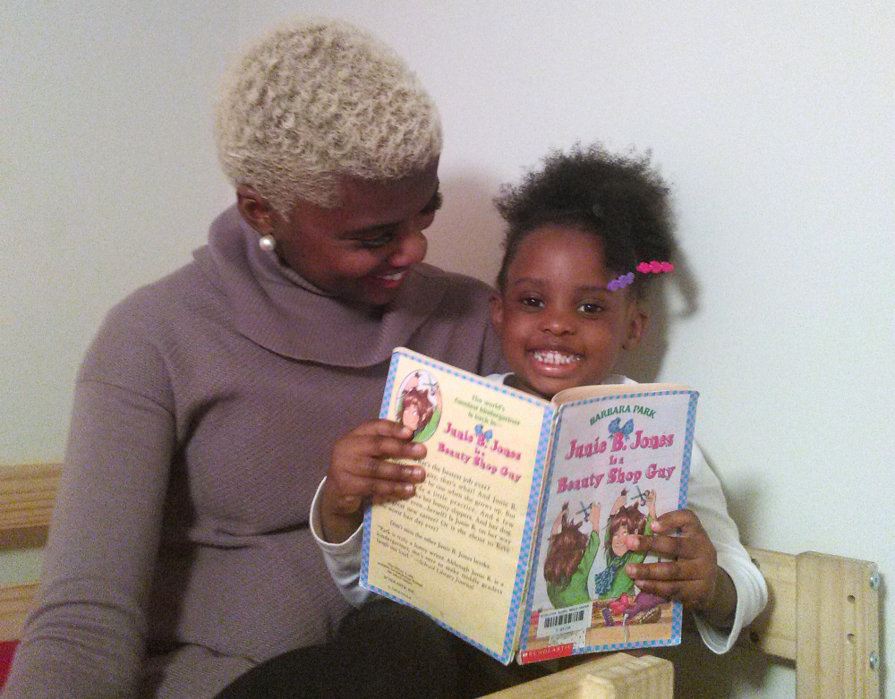 Kasey Woods poses with her daughter at their home in Waldorf, Md. Nearly three years ago, Woods put up a photo of her baby daughter in a pink top and huge afro wig that was left over from Halloween. The image has been liked, shared and commented upon several thousand times.