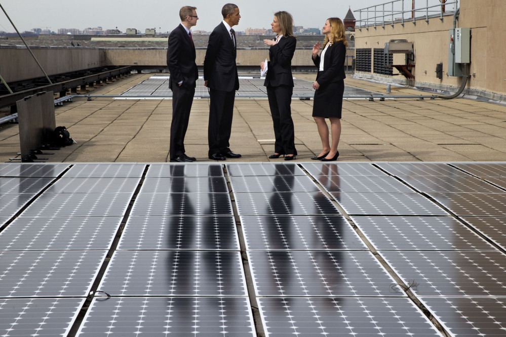 President Obama tours solar panels on the roof of the Energy Department in Washington on Thursday. Under Obama's executive order, the government must cut energy use in federal buildings by 2.5 percent every year through 2025.