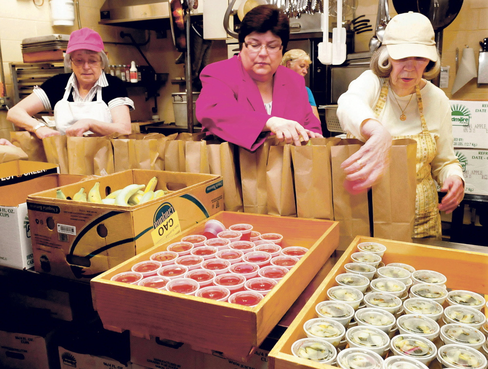 Linda Fossa, center, director of health and welfare for the city of Waterville, joined volunteers including Cheryl Gulliver, left, and Helen Cole to pack meals at the Muskie Center in Waterville on Thursday.