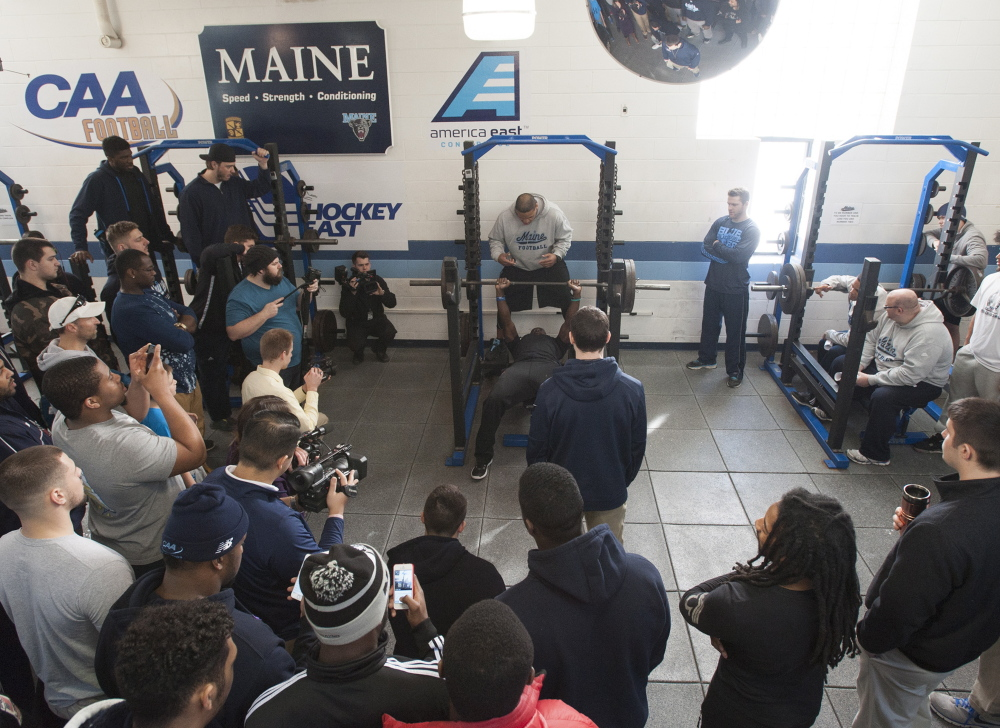 Teammates and media gather around UMaine defensive back Axel Ofori Jr. as he bench presses for Brandon Yeargan, a scout from the New England Patriots, at the UMaine weight room during Pro Day on Thursday in Orono.