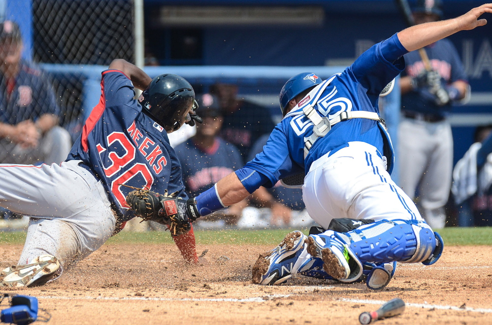 Boston second baseman Jemile Weeks slides in safely past the tag of Toronto catcher Russell Martin in the third inning of a 6-3 spring training loss by the Red Sox at Dunedin, Fla., on Thursday.