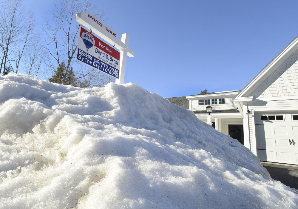 Mounds of snow linger Thursday at a Falmouth property listed for sale by David Banks, a Realtor with RE/MAX by the Bay in Portland. Pending home sales in Maine were down 4.1 percent in February compared with one year earlier, according to a RE/MAX report issued this week.