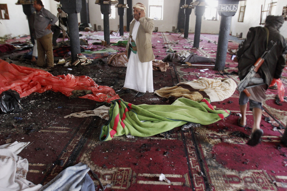 People stand amid bodies covered with blankets in a mosque after a suicide attack during the noon prayer in Sanaa, Yemen, on Friday.