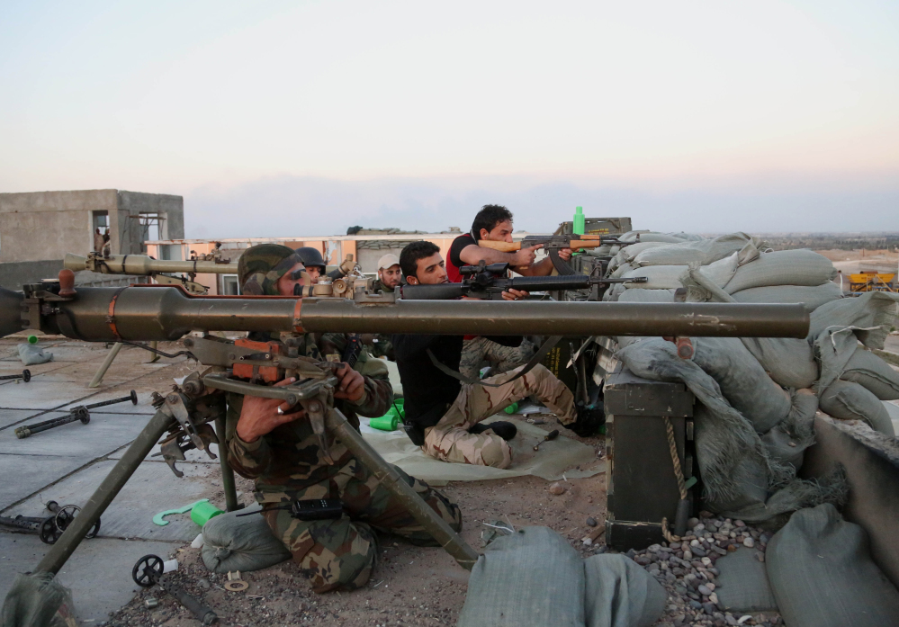 Iraqi security forces and allied Shiite militiamen battle Islamic State fighters in Tikrit last Sunday. The government and the militias are reported to be divided over tactics in the operation.