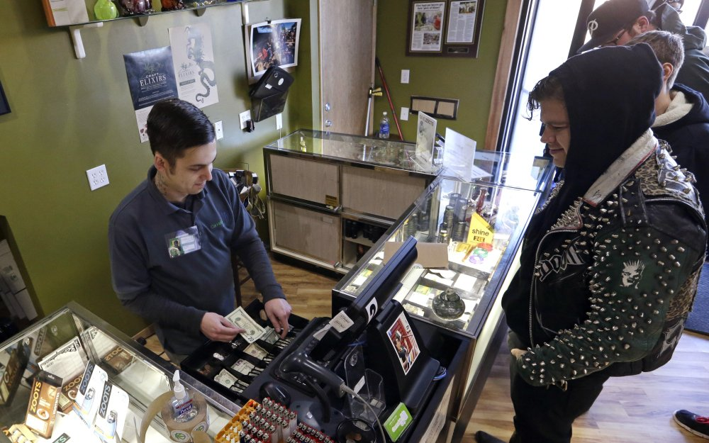 Cannabis City clerk John Golby, left, helps customers looking for marijuana products at the shop in Seattle. For the first time, most Americans want to legalize marijuana, according to the 2014 General Social Survey.