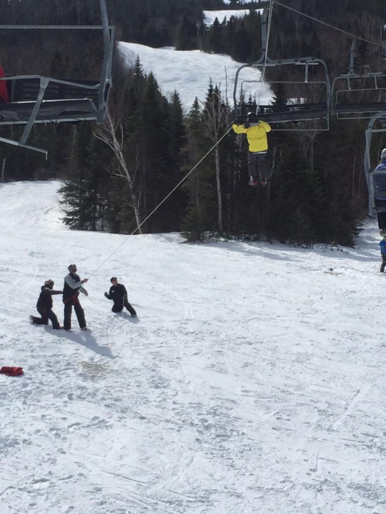 Sugarloaf employees work to lower a skier down from the King Pine quad chairlift Saturday after it rolled back several hundred feet. Photo courtesy of WCSH