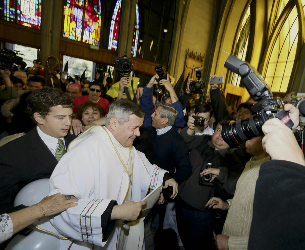 The Rev. Juan Barros is escorted into a cathedral for his ordination as bishop Saturday in Osorno, Chile, in a ceremony cut short by protesters who accuse him of covering up sex crimes by a priest disciplined by the Vatican.