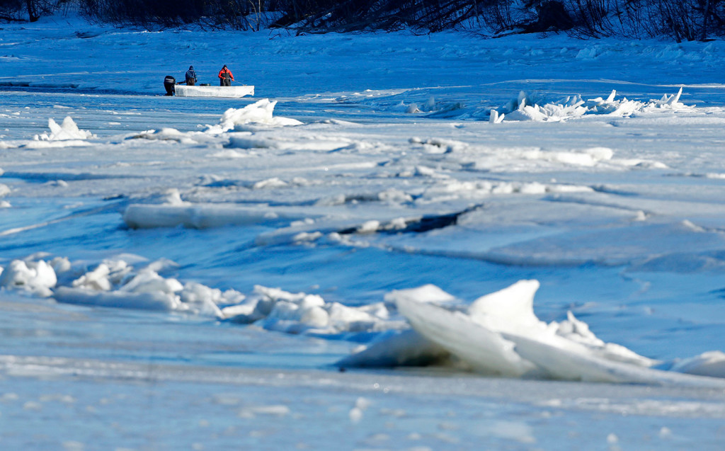 Men use a boat in an attempt to break ice on the Royal River in Yarmouth on Thursday. A state panel is examining the long-lasting snowpack and black river ice to determine the potential for ice jam flooding. The Associated Press/Robert F. Bukaty