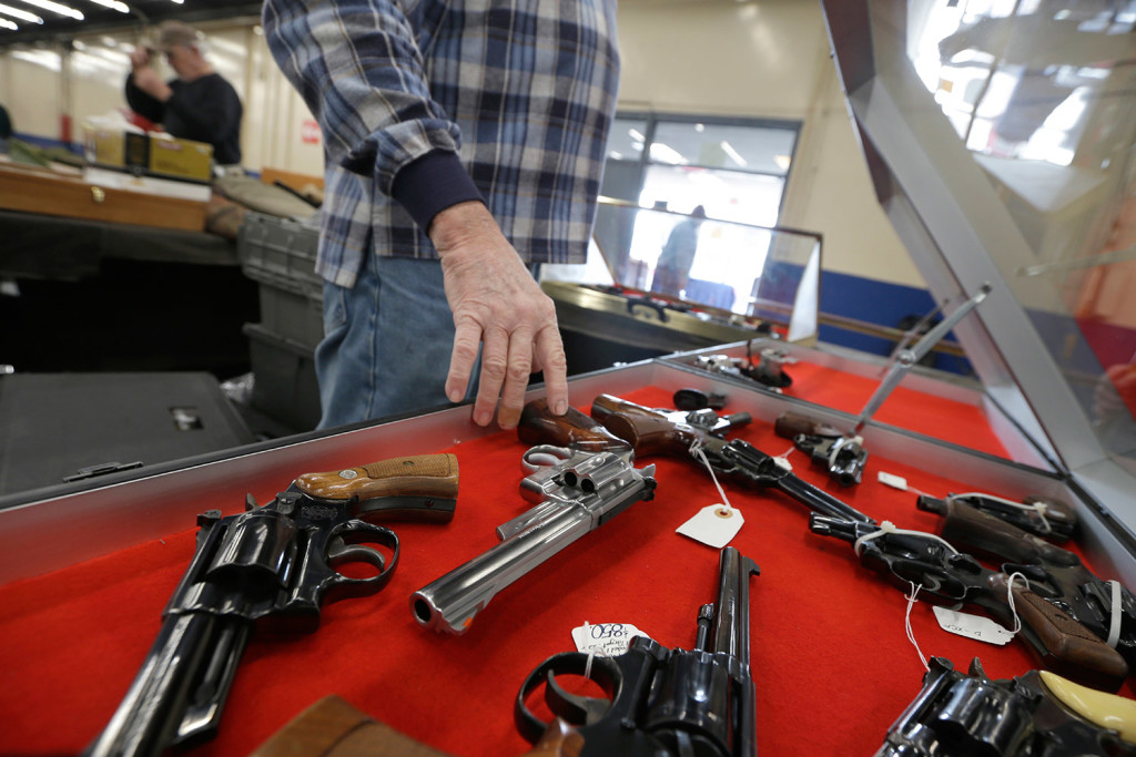 A dealer arranges handguns in a display case in advance of a February show at the Arkansas State Fairgrounds in Little Rock. A major U.S. trend survey finds that the number of Americans who live in a household with at least one gun is lower than it's ever been.
