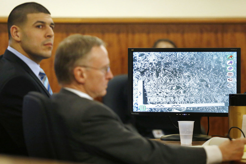 Aaron Hernandez and  his attorney, Charles Rankin, listen to testimony as a photograph of tire marks is displayed on a monitor during the trial. The Associated Press