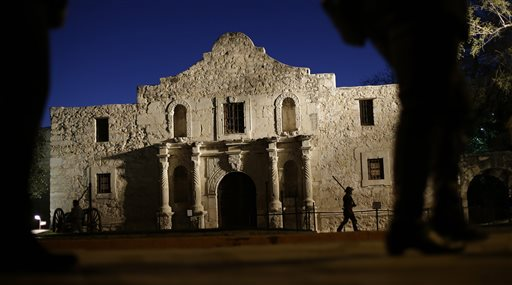 Dan Phillips, a member of the San Antonio Living History Association, patrols the Alamo during a pre-dawn memorial ceremony to remember the 1836 Battle of the Alamo and those who fell on both sides. The Daughters of the Republic of Texas filed suit Monday against the Texas General Land Office for control of more than 30,000 books and artifacts within the historic site's library. (The Associated Press File photo)