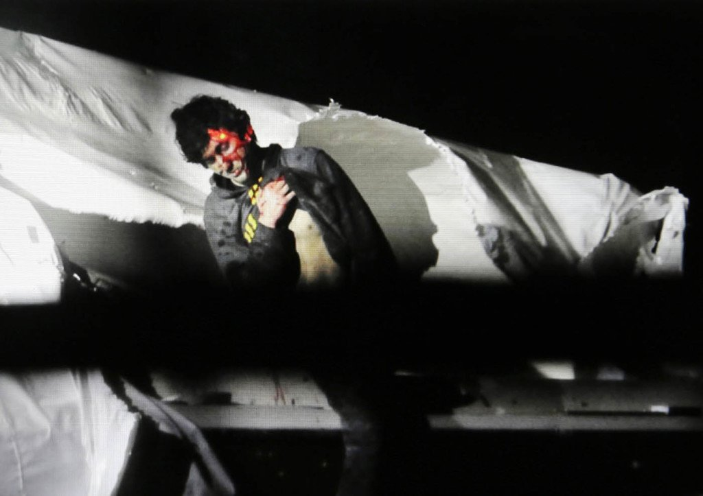 Boston Marathon bombing suspect Dzhokhar Tsarnaev, bloody and disheveled with the red dot of a sniper's laser sight on his head, emerges from the boat where he was captured in Watertown, Mass., on April 19, 2013. Massachusetts State Police photo