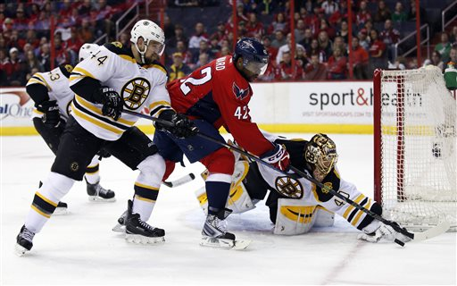 Bruins defenseman Dennis Seidenberg (44), Capitals right wing Joel Ward (42) and goalie Tuukka Rask (40) reach for the puck in the first period Sunday in Washington. The Associated Press