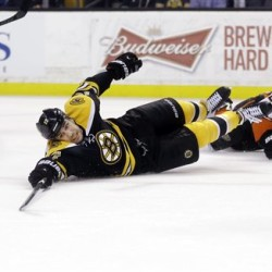 Bruins left wing Milan Lucic cannot reach the puck after being tripped by a Duck. (AP Photo/Elise Amendola)