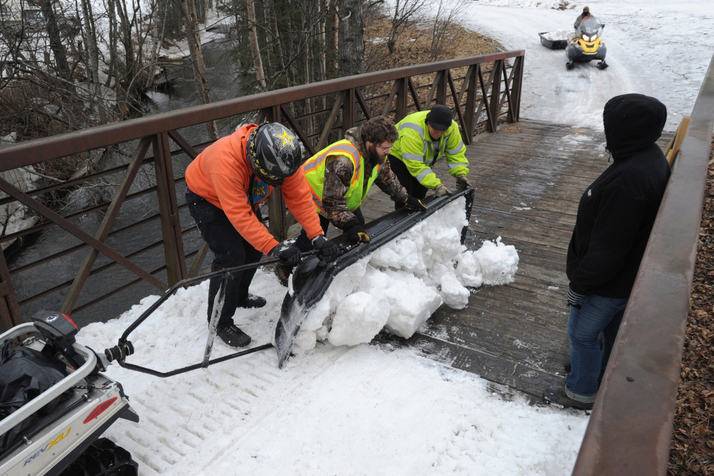 Parks and Recreation maintenance workers empty a sled load of snow from Goose Lake onto a snowless bridge in Anchorage, Alaska.  Crews have been moving snow into tunnels, covering bridges and bare spots in the trail in preparation for the ceremonial start of the Iditarod Trail Sled Dog Race.