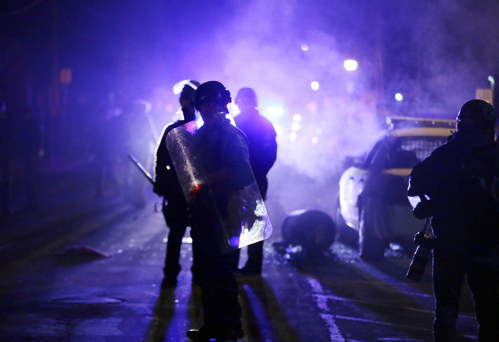 Police watch protesters as smoke fills the streets in Ferguson, Mo.,  after a grand jury's decision not to press charges in the fatal shooting of Michael Brown. A Justice Department investigation has found patterns of racial bias in the Ferguson police department and at the municipal jail and court. The Associated Press