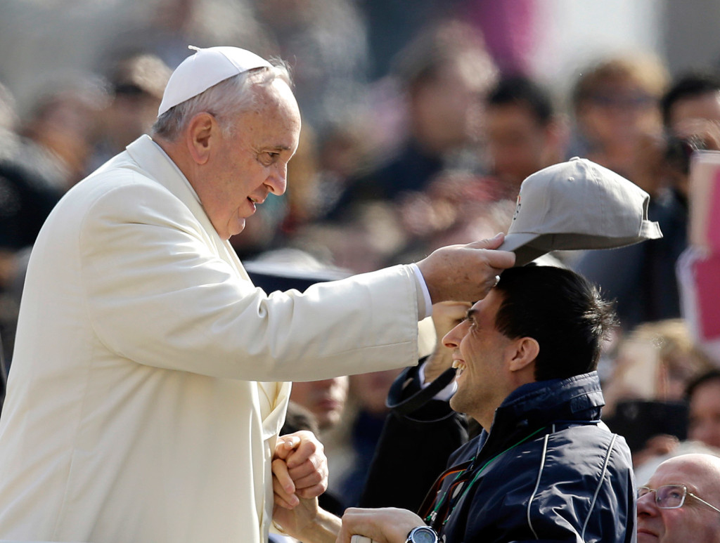 Pope Francis puts a cap on the head of a man as he arrives for his weekly general audience in St. Peter's Square at the Vatican on Wednesday.