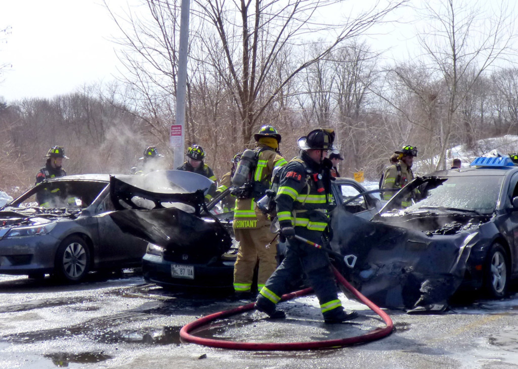 Firefighters finish extinguishing burning cars Tuesday in a Westbrook parking lot. The fire appeared accidental.