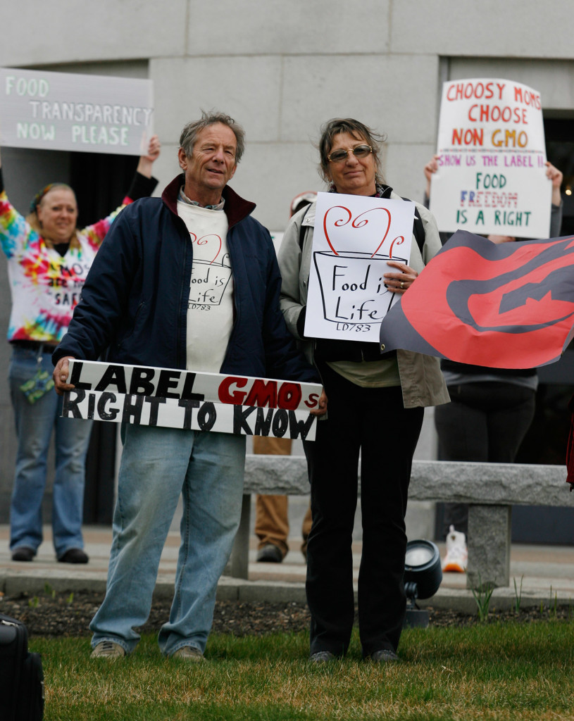 Farmers Michael and Pat Macfarlane hold signs outside the State House on Thursday in Augusta during a rally in support of a bill that would allow Maine's GMO labeling law to go into effect without relying on other states to take action.