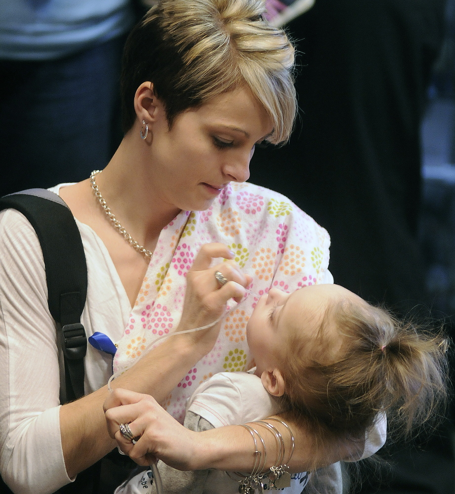 Jamie Davis clears the mouth of her daughter, Addilyn, on Monday before attending a hearing on a bill that would add Krabbe's disease to the list of disorders that newborns are screened for. Davis has raised awareness of the disease, a genetic disorder of the central nervous system, on a Facebook page followed by 107,000 people since her daughter was born with it in 2011.