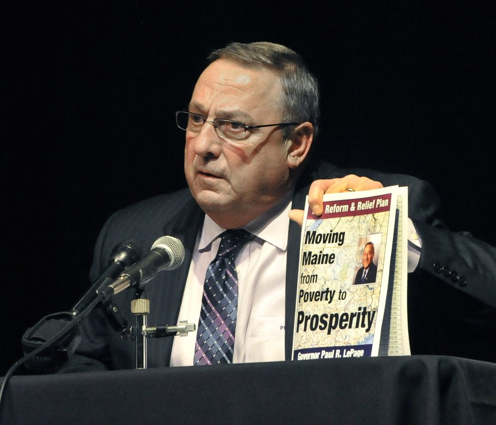 Gov. Paul LePage holds up a copy of his tax reform plan during Thursday night's town hall meeting in Saco. LePage continues to fight for his proposals, but he also has appeared resigned at times to seeing lawmakers reject key portions of his plan.