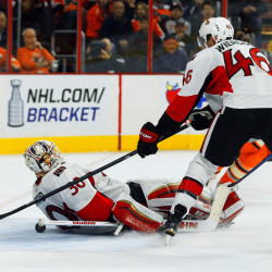 Ottawa Senators goalie Andrew Hammond, left, falls backward on to the puck while Patrick Wiercioch tries to keep it from sliding into the net in the second period at Philadelphia on Saturday.