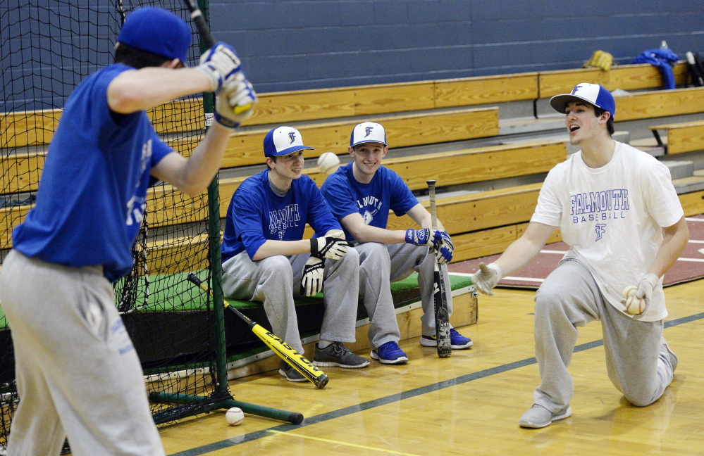Ryan Mucci, right, tosses a ball to Connor MacDowell as Caleb Lydick, center left, and Cal Inlow look on during a Falmouth High baseball practice. The four inseparable friends are playing one final baseball season together before going their separate ways to college.