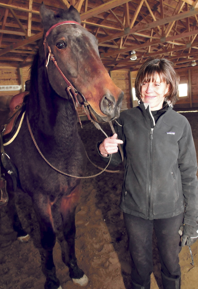 Debbie Hight stands with Postcard Jack, who has retired from harness racing and is training to be a saddle horse.