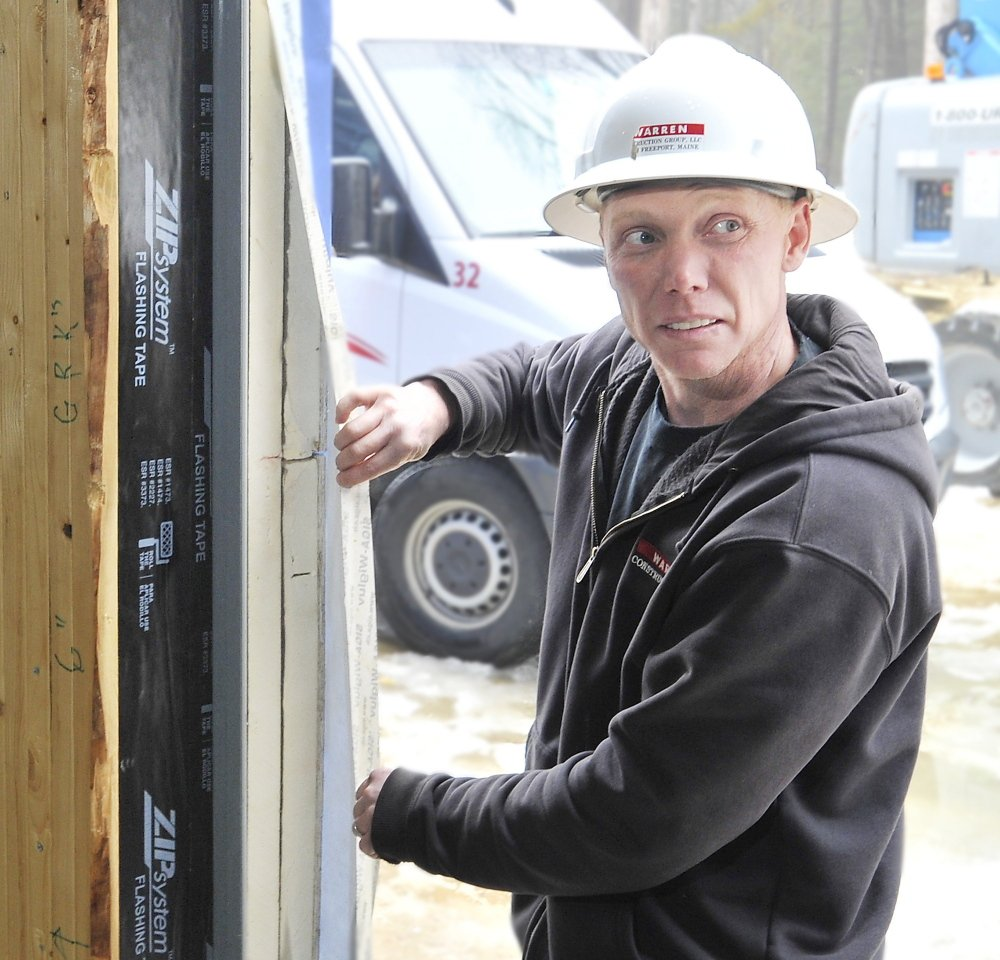 Mike Matthes, supervisor for Warren Construction Group, shows the six layers of material that create an airtight barrier in the walls of the new Friends School of Portland.
