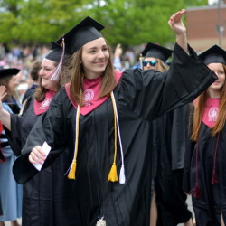 University of Maine at Farmington graduates wave to friends and family as they march down High Street during commencement ceremonies in Farmington on Saturday.
