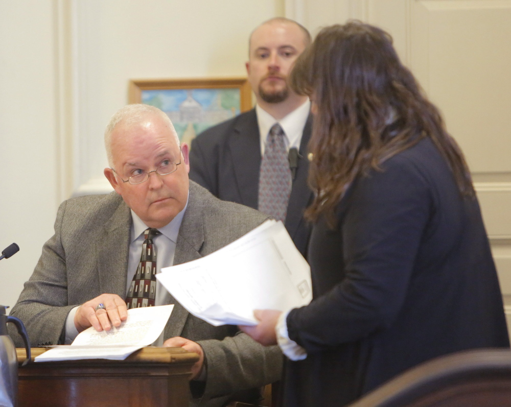 Defense attorney Amy Fairfield, right, presents Eliot Police Chief Theodor Short with documents during a proceeding in February related to allegedly falsified officer patrol reports.
