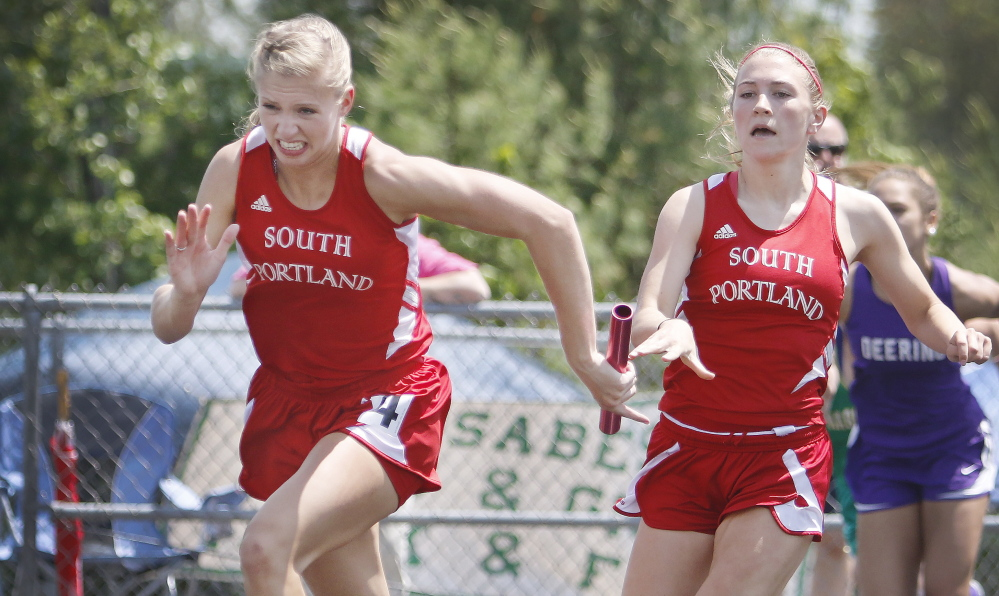 Callie O'Brien of South Portland, right, makes the handoff to teammate Lauren Magnusson during the 400-meter relay. South Portland was third in the girls' meet, behind Thornton Academy and Scarborough.