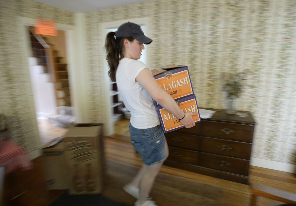 Caroline Ferguson carries boxes out of her Brunswick apartment. Saying goodbye to college was a gradual process for her and her housemates.
