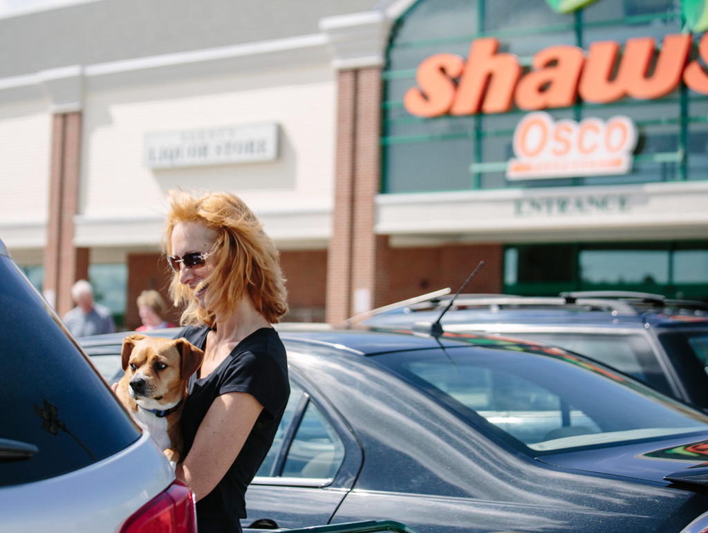 Carey Anne Nason holds her dog Milo after loading groceries from Shaw's into her car in Biddeford on Wednesday. Nason said she shops there because the store's butcher will cut bones small enough for her dog to chew.