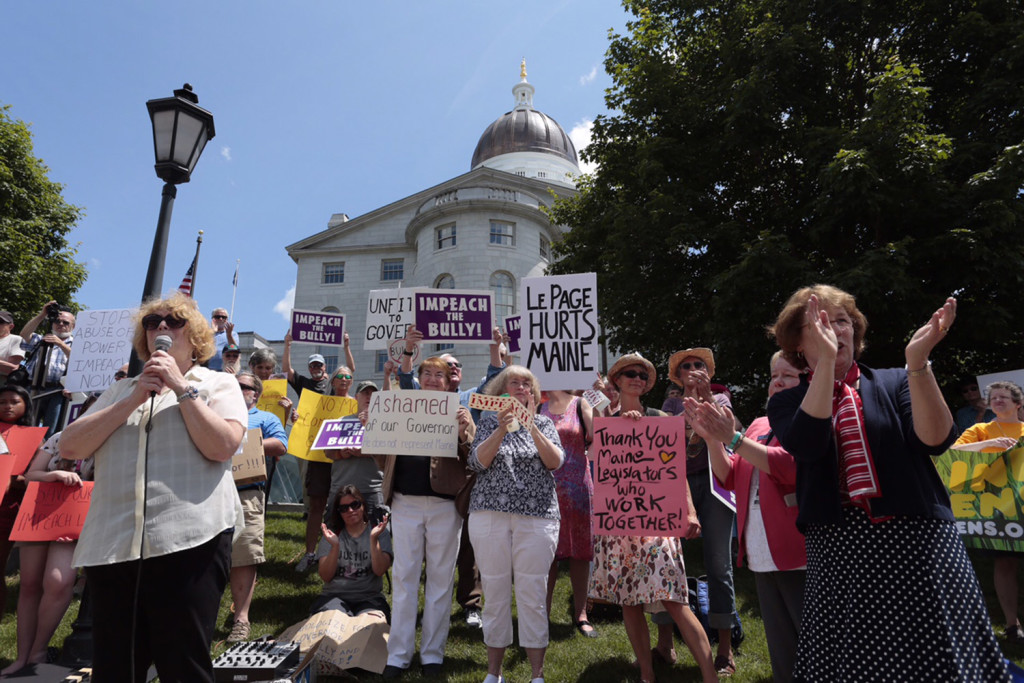 Protesters critical of Gov. Paul LePage gather outside the State House in Augusta on Tuesday.