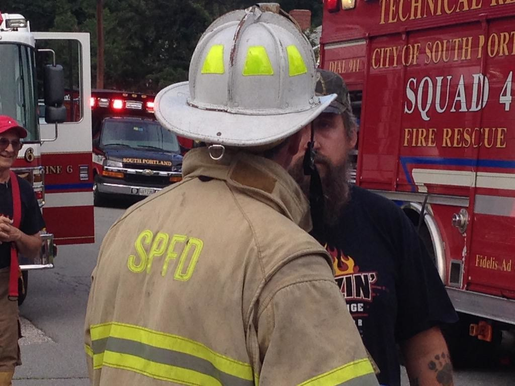 A firefighter talks to a man at the scene of a fire on Burwell Avenue in South Portland. (WCSH photo)