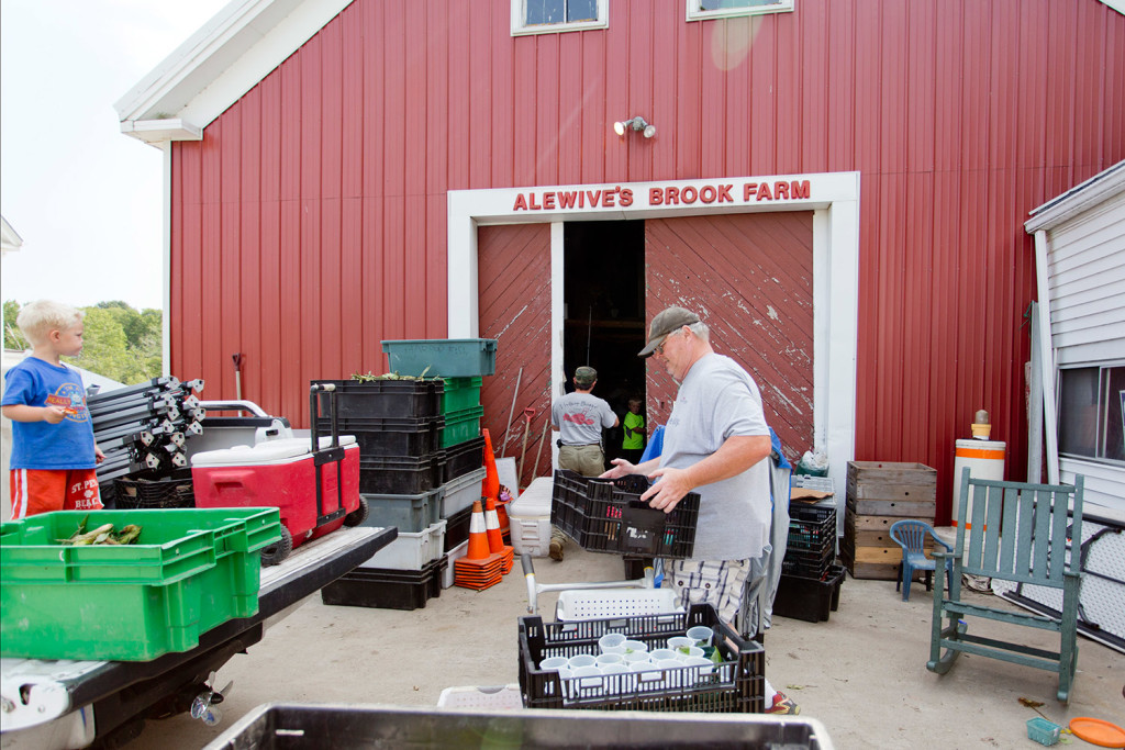 John Gildard carries a crate of fruit while he works with Lincoln Jordan, at rear, and Jordan's nephews Bennett Rideout, 3, and Sam Rideout, 6, to unload at Alewive's Brook Farm in Cape Elizabeth after attending a farmers market in Scarborough on Monday. The farm is one of many that are urging Maine's university system to buy from local farms.