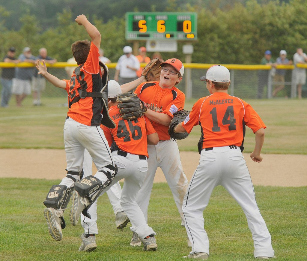 Biddeford players rush the mound to celebrate their team's 5-0 win over Hall-Dale in the Maine Little League championship baseball game Thursday.