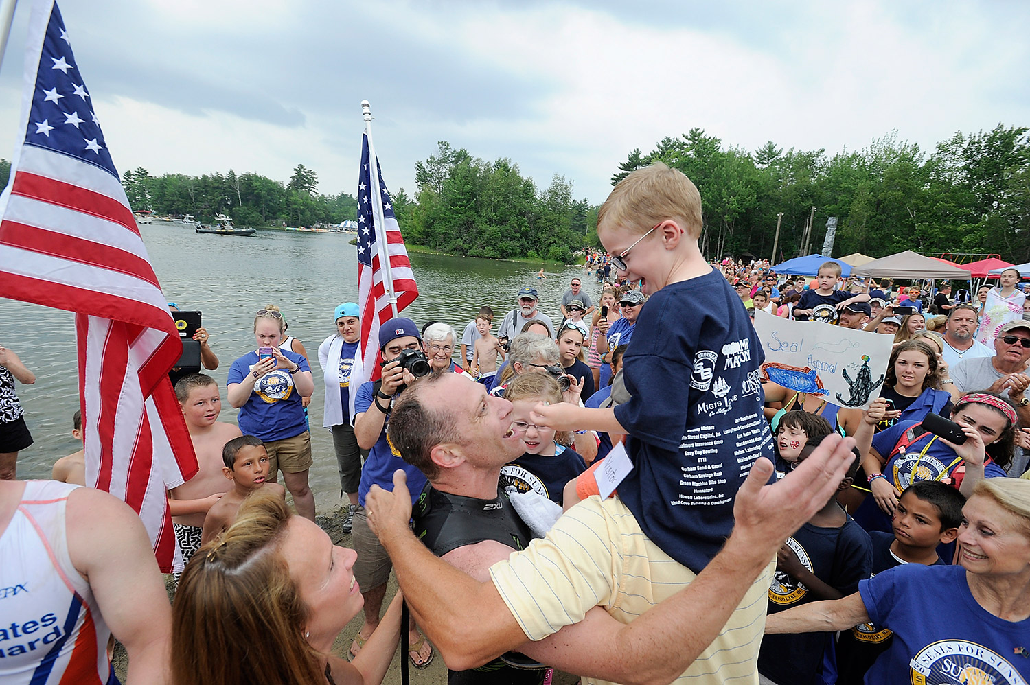 A Navy SEAL is welcomed by his family after completing the Summit to Sunshine Challenge, a reverse triathlon, at Point Sebago Resort on Thursday. The challenge consists of a 7.6-mile run down Mt. Washington, an 83.4-mile bike ride from New Hampshire to Sebago Lake, and then a 3.9-mile swim ending at Point Sebago Resort.