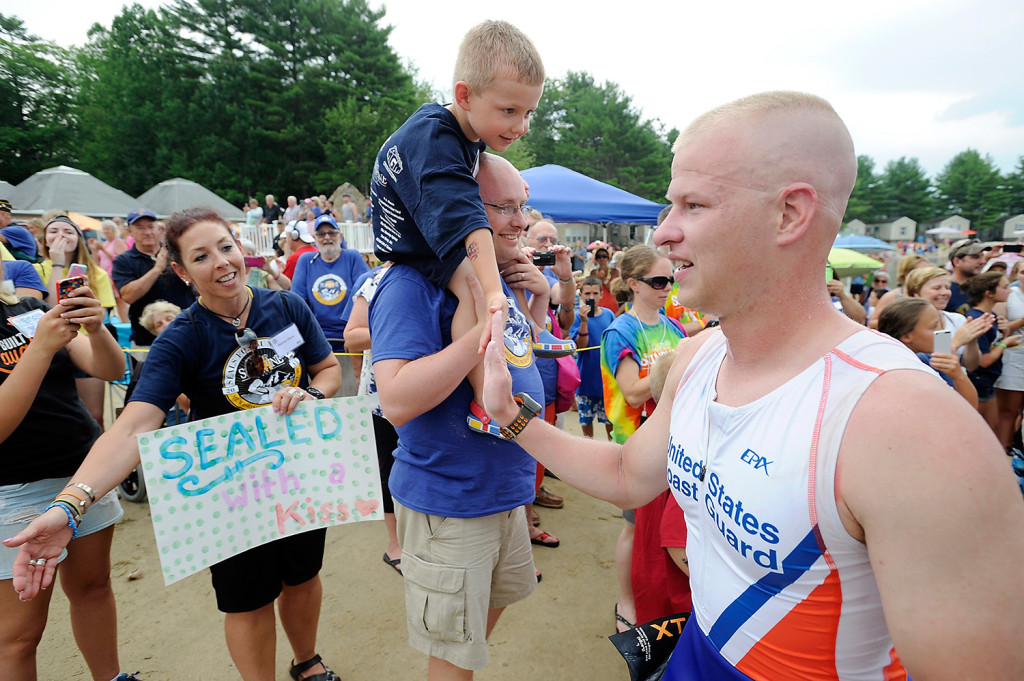Family members and Camp Sunshine supporters greet Navy SEALs at Point Sebago Resort as they complete a fundraising reverse triathlon.
