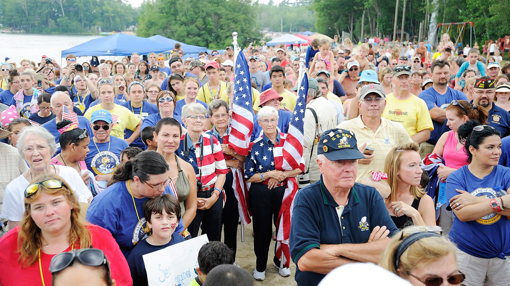 "The ""Flag Ladies,"" from left, Elaine  Green, Carmen Footer and Joanne Miller, are surrounded by a crowd of people from Camp Sunshine, friends and tourists as they watch five Navy SEALs complete the Summit to Sunshine Challenge, a reverse triathlon, at Point Sebago Resort. The goal was to raise more than $100,000 to sponsor Camp Sunshine stays for military and special-operations families that have a child diagnosed with a life-threatening illness."