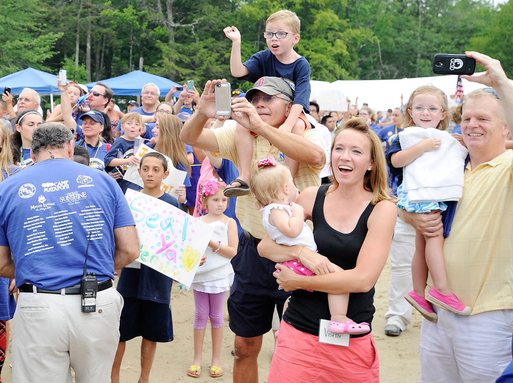 The family of one of the active-duty Navy SEALs who completed the Summit to Sunshine Challenge, a reverse triathlon, at Point Sebago Resort greet them as they arrive at the beach Thursday.