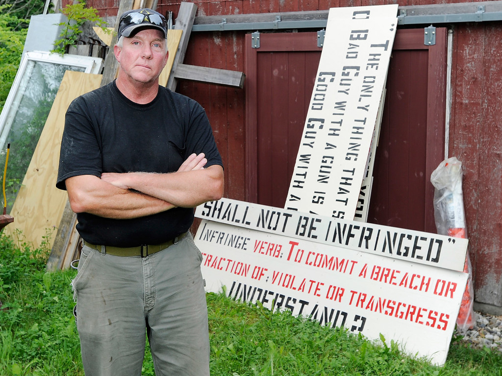 Linc Sample, who displays controversial signs about guaranteed rights in the Constitution, stands with a sign he planned to put up Wednesday. Gordon Chibroski/Staff Photographer