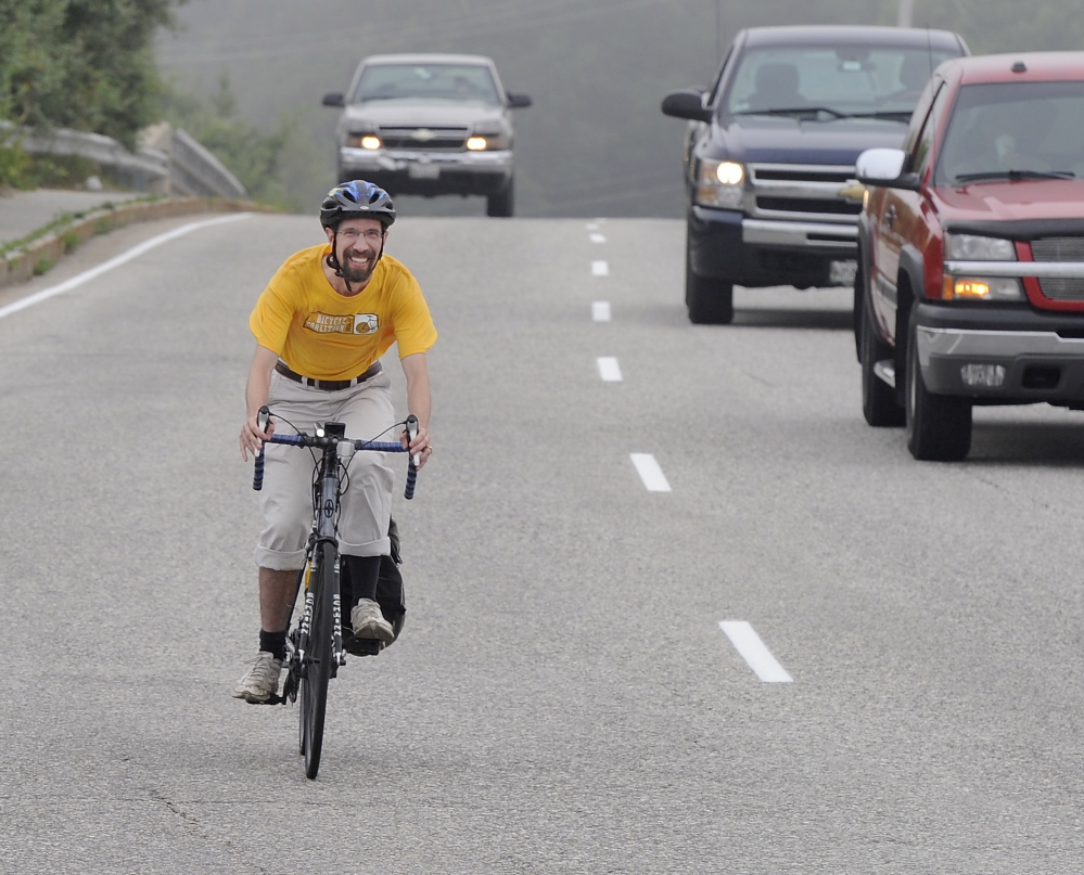 """John Brooking """"controls the lane"""" near the Maine Mall in South Portland. He and other bicycle educators say riding near the middle of the road is sometimes necessary for safety."""