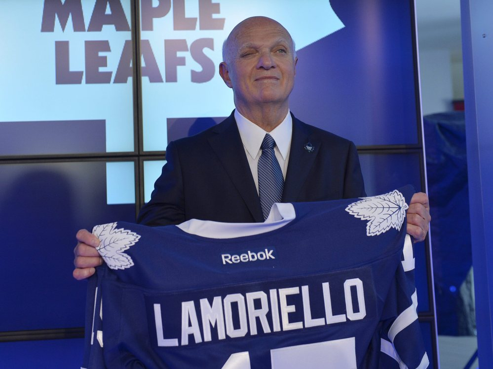 Lou Lamoriello holds up a Maple Leafs jersey at a news conference introducing him as Toronto's new general manager after 27 years with the Devils.