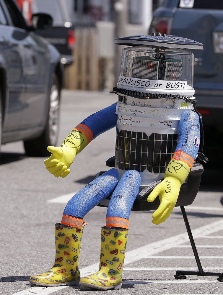 A car drives by HitchBOT, a hitchhiking robot, in Marblehead, Mass. The Associated Press