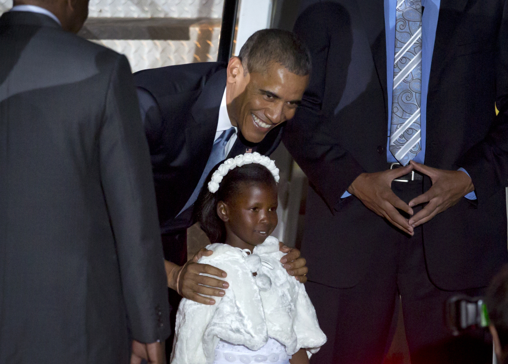 President Obama poses for a picture with Joan Wamaitha, 8, who gave him flowers at the Jomo Kenyatta International Airport in Nairobi, Kenya, on Friday.
