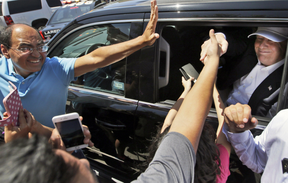 Supporters reach out to greet Republican presidential hopeful Donald Trump as he leaves a stop to speak to supporters and the media in Laredo, Texas, on Thursday.